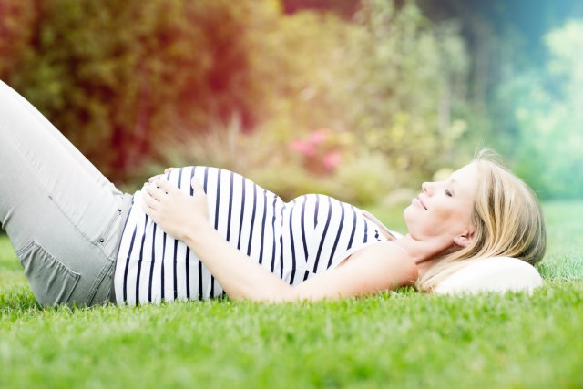 Беременная женщина на зеленой лужайке