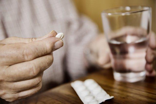 Белая таблетка и стакан воды