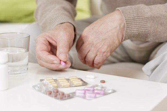 Таблетки и руки пожилого мужчины