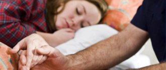 Мужчина держит спящую девушку за руку