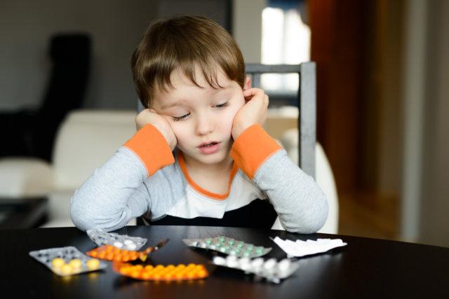 Ребенок и таблетки на столе